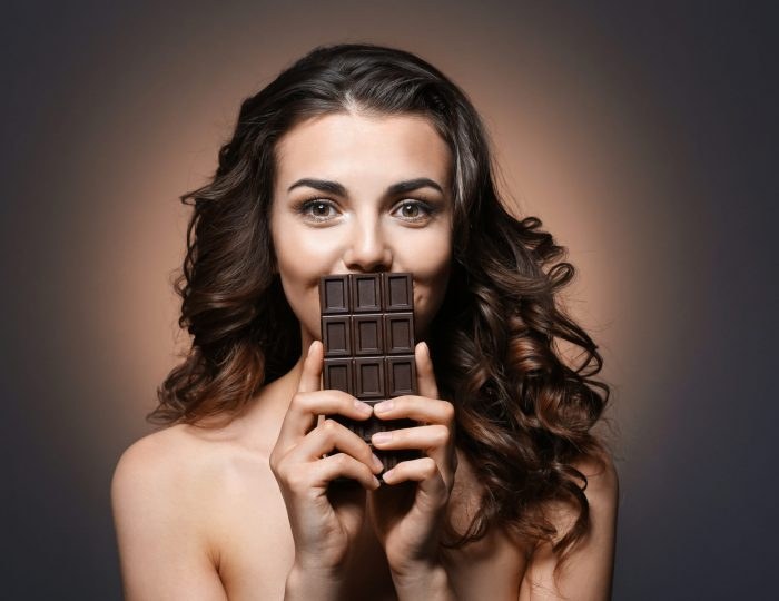 Beautiful girl with chocolate on dark background