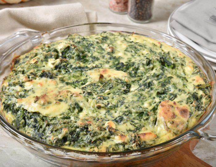 A crustless homemade spinach and cheese quiche cooling on the table