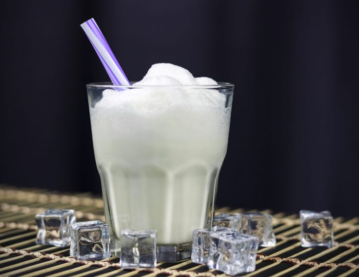 milkshake, in a glass with a straw and ice cubes, on a dark background