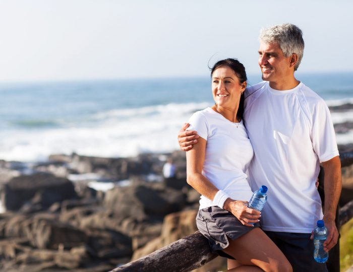 happy mature couple relaxing after exercise at the beach