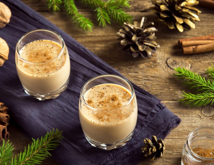 Eggnog with cinnamon in glasses over rustic wooden background with Christmas decor  - homemade traditional festive drink for Christmas time