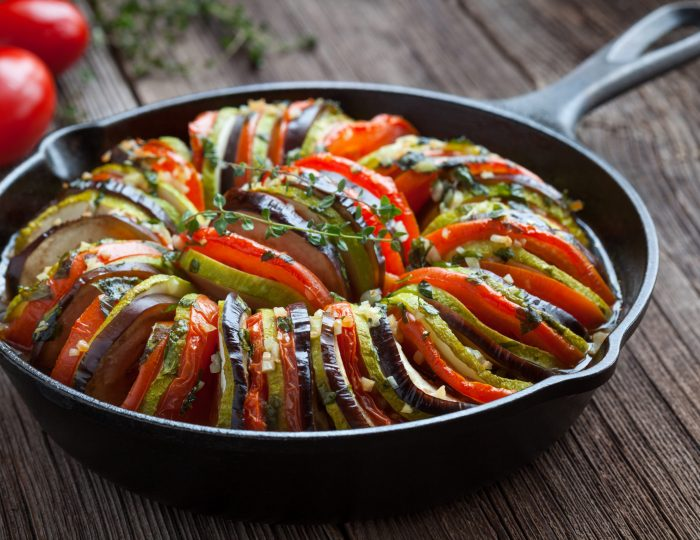 Traditional homemade vegetable ratatouille baked in cast iron frying pan healthy diet french vegetarian food on vintage wooden table background. Rustic style